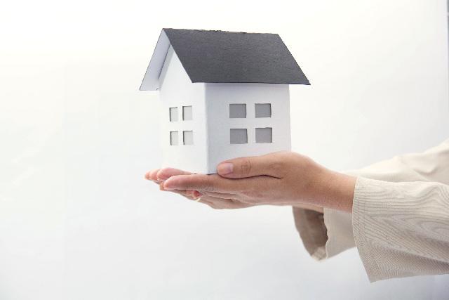 家の模型と女性の手
